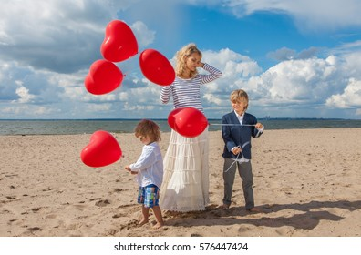 Portrait mother and two boys with red heart balloons on the beach in sunny day