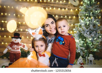 portrait of mother and two children at christmas tree