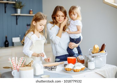 Portrait of a mother and two cute little girls baking cupcakes in the kitchen