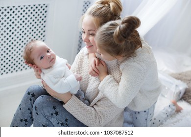 Portrait of mother with two daughters in white room near window. happy family mother and two children, son and daughter in bed playing. Woman and two young girls in bed playing and smiling