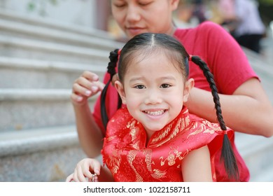 Portrait of Mother tying her daughter's hair. Two tied ponytails hairs. Child girl looking at camera.