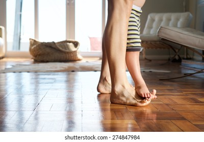 Portrait of a mother walking at home with child standing on her feet