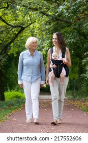 Portrait of a mother walking outdoors with grandmother and baby in sling