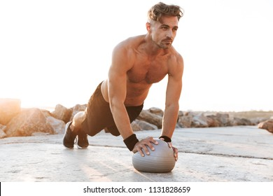 Portrait of a motivated shirtless sportsman doing exercises with small fitness ball outdoors