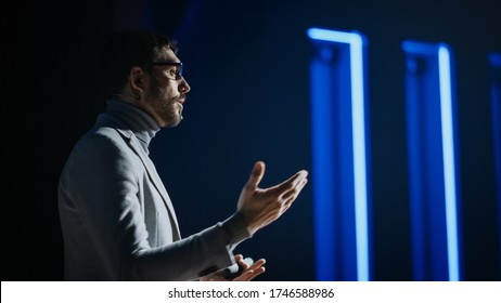 Portrait of Motivational Speaker Wearing Glasses, Talking about Happiness, Self, Success and How Better More Productive Self. Tech Startup Presenter Pitching. Cinematographic Light