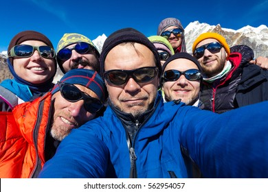 Portrait of Mountain Climbers Team emotional happy Faces at top of high Altitude Summit in extreme Sport outwear and gear