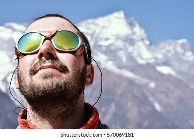 Portrait of a mountaineer at high peaks background.