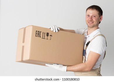 Portrait of mover with cardboard box in hands on gray background. Relocation services man holds box. Loader in uniform
