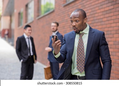 Portrait of multi ethnic business team. Three happy smiling men standing against the backdrop of the city. The surprised African-American man  talking on the phone , other is Chinese and European