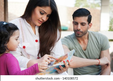 portrait of a multi ethnic family in outdoor, mother and reading a story for her little daughter.