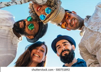 Portrait of multi ethnic friends standing in circle and looking down at camera