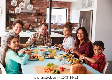 Portrait Of Multi Generation Family Enjoying Meal Around Table At Home Together