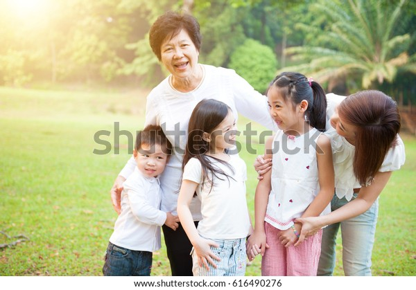 Portrait of multi generations Asian family at nature park. Grandmother, mother and grandchildren outdoor fun. Morning sun flare background.