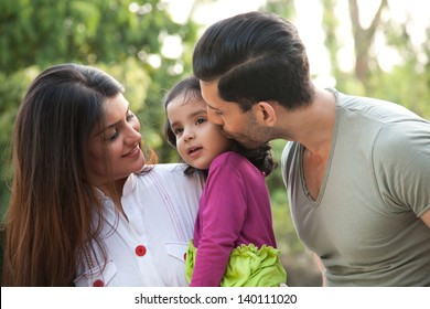 portrait of a multi racial family, father kissing the daughter. Indian family of three.