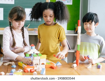 Portrait Of Multi-Cultural Children  playing with colorful blocks on table in a primary interracial classroom. Education brain training development for children skill concept.