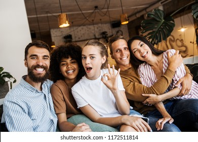 Portrait of multicultural millennial young friends looking at camera, happy multiracial people group having fun in coffeehouse together, diverse african and caucasian students bonding at cafe meeting