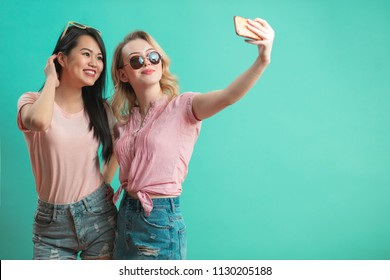 portrait of multicultural student girls taking selfie on smartphone together isolated on blue