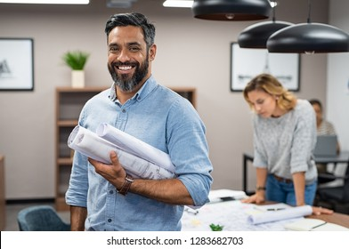 Portrait of multiethnic architect with blueprints in creative office. Mature middle eastern contractor holding roll of architectural projects while looking at camera. Happy latin man in casual.