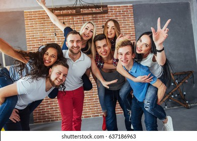 portrait of multi-ethnic boys and girls with colorful fashionable clothes holding friend and posing on a brick wall, Urban style people having fun, Concepts about youth and togetherness lifestyle.