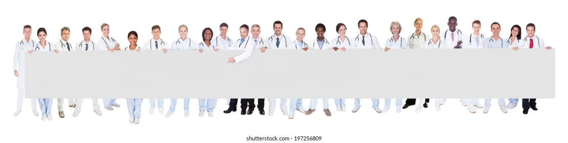 Portrait of multiethnic doctors holding blank banner against white background