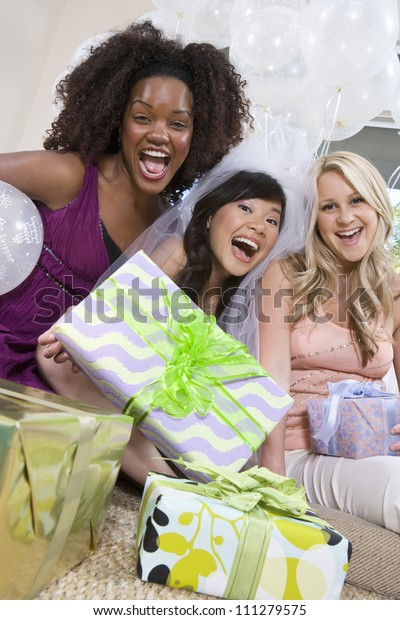 Portrait of multiethnic friends with gifts screaming at party