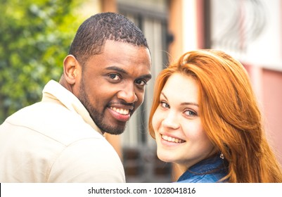 Portrait of multiethnic man and young woman walking outdoors - Happy multiracial couple at beginning of love story - Integration concept with boyfriend and girlfriend dating on warm retro filter