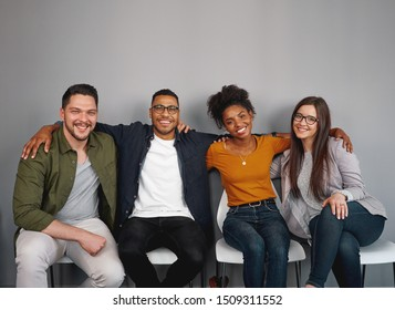 Portrait of multiethnic young friends sitting together happily with their arms around each other on chair smiling and looking at camera