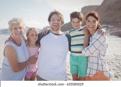 Portrait of multi-generated family embracing at beach during sunny day