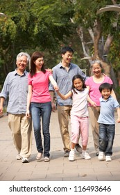Portrait Of Multi-Generation Chinese Family Walking In Park Together