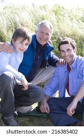 Portrait of multi-generation family crouching on beach