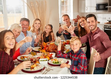 Portrait Of Multi-Generation Family Sitting At Table Making A Toast Whilst Eating Thanksgiving Meal At Home Together