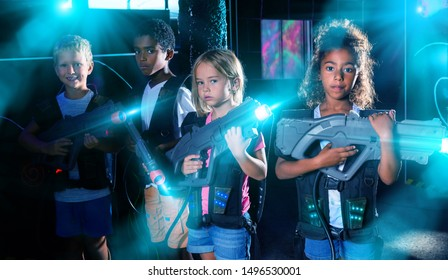 Portrait of multiracial team of happy preteen kids with laser guns during lasertag game on dark arena