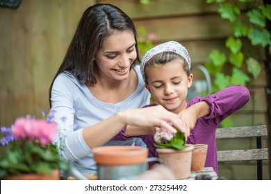 Portrait of mumy and her little girl doing gardening