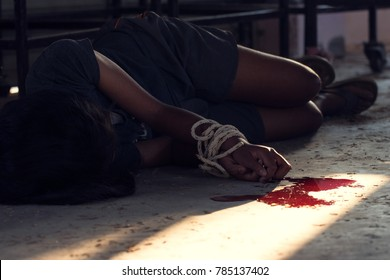 Portrait of murder concept, Close up Hands tied with rope and have bleeding on the cement floor in the room. Use as background and accompanying articles. Soft focus.