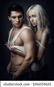 portrait muscular handsome sexy guy with pretty woman on dark background, look on camera