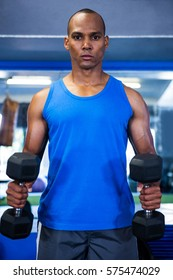 Portrait of muscular man exercising with dumbbells in fitness studio