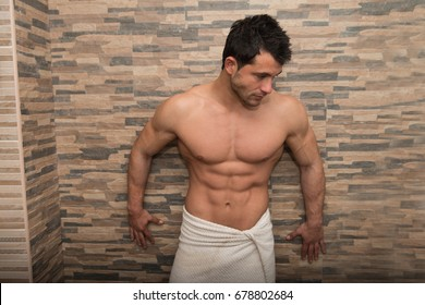 Portrait Of A Muscular Man In The Modern Room Where He Poses In Towel