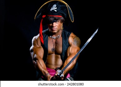 Portrait of a muscular man in a pirate costume. Aggressive man with a sword on a black background