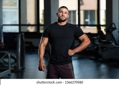 Portrait Of A Muscular Man In Shorts And Black T-shirt Posing In The Gym