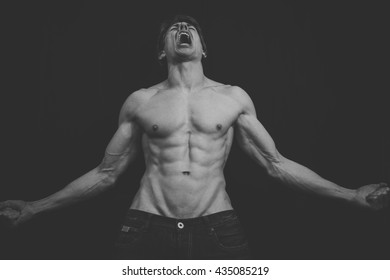 Portrait of a muscular man in a studio.  He is very lean and muscular, his abs very defined.  Fade has been used to make the image more atmospheric in feel.  He is portraying uncontrollable anger.