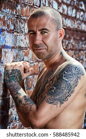 Portrait of a muscular man with tattoo standing on a street by a brick wall. Tattoo concept.