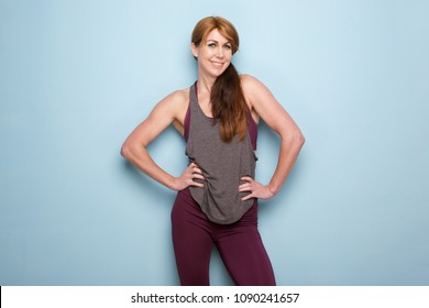 Portrait of muscular mature woman standing against blue wall with hands on hips