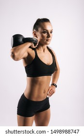 Portrait of muscular sexy young woman in black sportswear is holding kettlebell weight on shoulder, on white isolated background