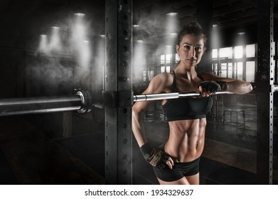 Portrait of a muscular woman near a power rack with a barbell. A dark, smoke-filled gym with large windows. Bodybuilding, powerlifting, fitness concept. Mixed media