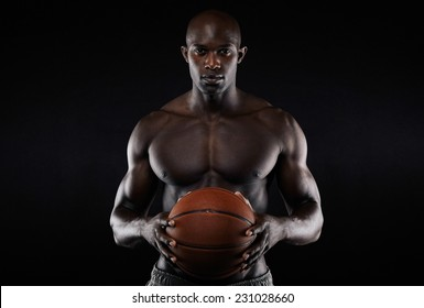 Portrait of muscular young man shirtless holding a basketball. Afro american basketball player against black background.