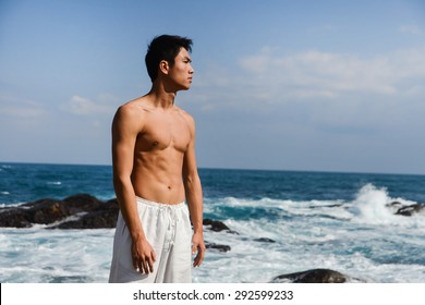 Portrait of Muscular young man standing on rocks at beach