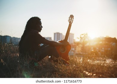 Portrait of musician African man  wearing dreadlocks holding guitar outdoor on city sunset