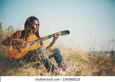 Portrait of musician African man  wearing dreadlocks holding guitar outdoor