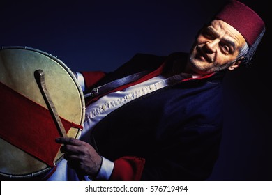 Portrait of a musician from Balkan, Macedonian style, wearing a fez hat and tapan drum.
