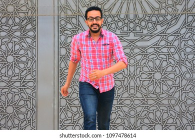portrait of a muslim bearded young man outdoor , wearing red plaid shirt with a smiling face .